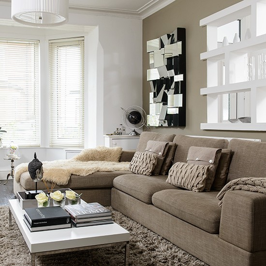 Neutral modern living room with beige sofa and mirror ...