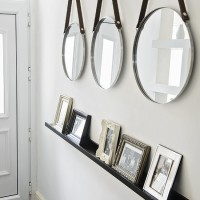 Modern white hallway with trio of circular mirrors
