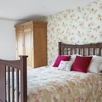 Country bedroom with floral wallpaper and brown furniture