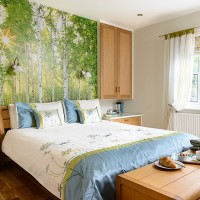 Sunny bedroom with woodland mural and floral bedding