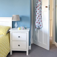 Traditional bedroom with blue wall and white bedside table