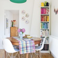 White dining room with colourful accessories and bookcase