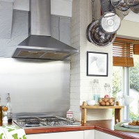 Rustic country kitchen with stainless steel splashback and hob