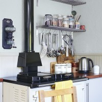 Country kitchen with range cooker and stainless-steel utensils