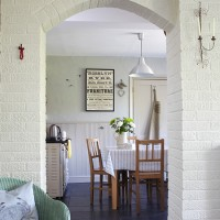 Pale dining room with painted brickwork and industrial pendant light