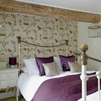 Country bedroom with birdcage statement wallpaper