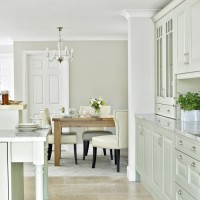 Classic dining area with kitchen and pale green cabinetry