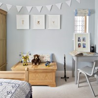 Child's bedroom with pale blue walls and bunting