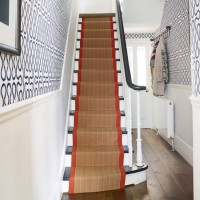 Smart hallway with feature wallpaper and red-trimmed stair runner