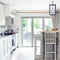 Country kitchen-diner with pale green cabinetry