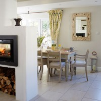 Neutral open-plan dining room with central woodburner
