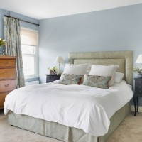 Pale blue bedroom with grey upholstered bed
