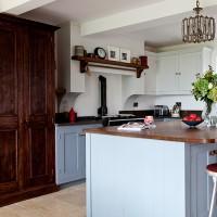 Blue kitchen with dark wood worktops