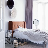 Modern white bedroom with purple curtains and velvet headboard