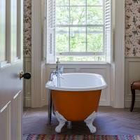 Impressive bathroom with orange tub and hummingbird wallpaper