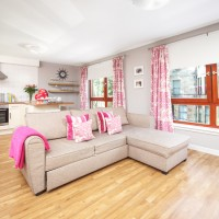 Open-plan living area with pink toile and striped accents