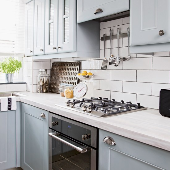 Pale blue kitchen with white metro tiles and black oven for Metro tiles kitchen ideas