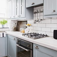 Pale blue kitchen with white metro tiles and black oven