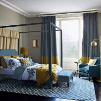 Teal blue and mustard bedroom with modern four-poster bed