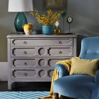 Bedroom corner with chest of drawers and teal armchair