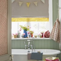 Joyful bathroom with green painted panelling and bunting