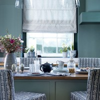 Teal kitchen with glass pendants and breakfast bar