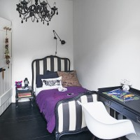 Monochrome bedroom with striped fabric headboard and black floorboards