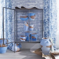 Contemporary dining area with inky blue wallpaper and display cabinet