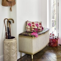 Vintage-inspired hallway with antique ottoman and umbrella stand