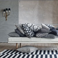 Monochrome living room with patterned cushions and striped rug