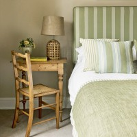 Country bedroom with green striped headboard