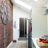 Modern galley kitchen with exposed brick wall