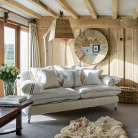 Country living room with wooden wall panels and upholstered sofa
