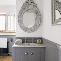 Bathroom with grey painted cabinetry and mirror