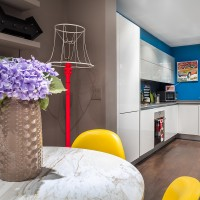 Kitchen-diner with vibrant blue walls and yellow chairs