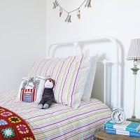 All-white bedroom with metal bedstead and striped bed linen