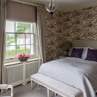 Classic bedroom with toile du Jouy wallpaper and gingham bench