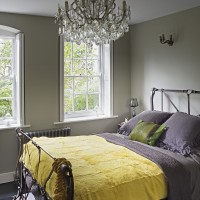 Sophisticated bedroom with iron bedstead and ornate chandelier