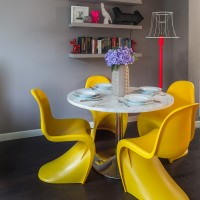 Grey dining room with bright yellow reproduction designer chairs