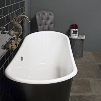 Gothic-inspired bathroom with freestanding bath and black tiling