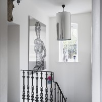 Classic white hallway with stainless-steel artwork and pendant