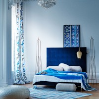 Contemporary blue bedroom with low-level bed and patterned curtain