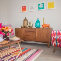 Colourful living room with wooden sideboard and framed prints