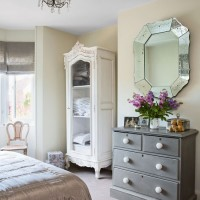 French-inspired bedroom with white armoire and grey storage