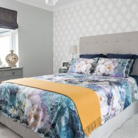Grey-toned bedroom with floral bed linen and mustard throw