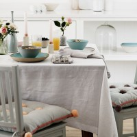 Smart dining room with linen tablecloth and pom-pom seat cushions