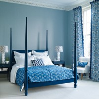 Indigo blue bedroom with dramatic four-poster bed and patterned soft furnishing