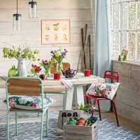 Country dining room with reclaimed timber panelling and pretty accessories
