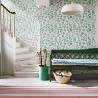 Hallway with green floral wallpaper and painted bench