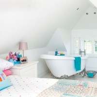 Bright white bedroom with roll top bath